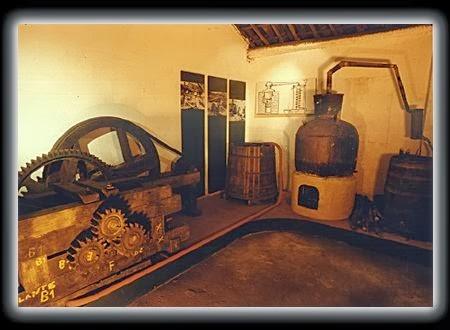 Um pequeno alambique de cobre e uma moenda mecânica. Ainda hoje no Brasil embora haja a produção industrial de cachaça, algumas empresas adotam a produção artesanal.