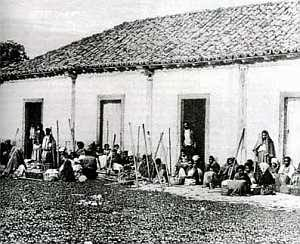 Foto do século XIX mostrando alguns escravos diante da senzala. Possivelmente essa senzala fosse de uma fazenda de café.